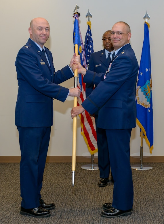U.S. Air Force Col. Danny Davis, 81st Mission Support Group commander, takes the 81st Communications Squadron guidon from Lt. Col. Jerry Hambright, outgoing 81st CS commander, during the 81st CS change of command ceremony in the Roberts Consolidated Aircraft Maintenance Facility Auditorium at Keesler Air Force Base, Mississippi, June 28, 2018. The passing of the guidon is a ceremonial symbol of exchanging command from one commander to another. (U.S. Air Force photo by Andre' Askew)