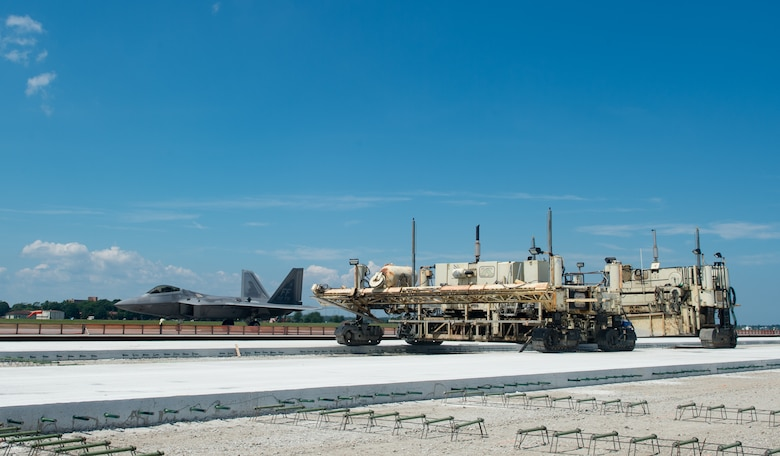 """A U.S. Air Force F-22 Raptor assigned to the 1st Fighter Wing taxis past the slip form paver at Joint Base Langley-Eustis, Virginia, June 29, 2018. The Brownie Pad on the Langley Air Force Base flightline, is receiving a 48,000-square-yard upgrade, as part of an $11 million, three-phase project and will be called the """"East Ramp,"""" upon completion of the 10-month construction in October 2018. (U.S. Air Force photo by Staff Sgt. Carlin Leslie)"""