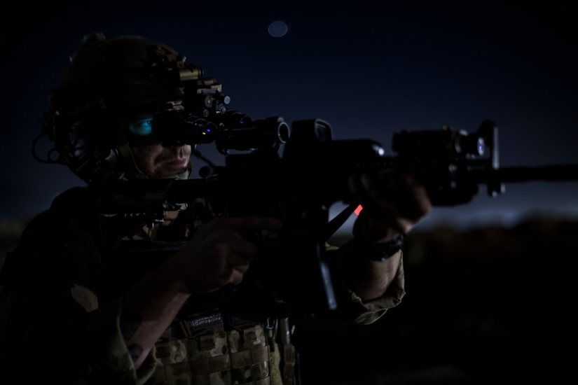 Pararescue airman aims rifle.