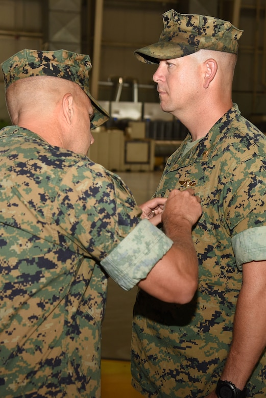 U.S. Marine Corps Col. Bret Ritterby, Marine Aviation Training and Support Group 22 commanding officer, pins a Meritorious Service Medal onto Maj. Andrew Armstrong, Marine Corps Detachment Goodfellow outgoing commanding officer, during the Marine Corps Detachment Goodfellow Change of Command at the Louis F. Garland Department of Defense Fire Academy on Goodfellow Air Force Base, Texas, July 10, 2018. The change of command is a transfer of total responsibility, authority and accountability from one Marine to another. (U.S. Air Force photo by Staff Sgt. Joshua Edwards/Released)