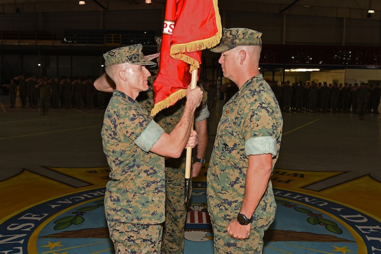 U.S. Marine Corps Lt. Col. Earl Patterson, Marine Corps Detachment Goodfellow incoming commanding officer, takes the guideon from Maj. Andrew Armstrong, Marine Corps Detachment Goodfellow outgoing commanding officer, during the Marine Corps Detachment Goodfellow Change of Command at the Louis F. Garland Department of Defense Fire Academy on Goodfellow Air Force Base, Texas, July 10, 2018. While holding the guideon, Patterson received verbal orders to lead the Marine Corps Detachment Goodfellow. (U.S. Air Force photo by Staff Sgt. Joshua Edwards/Released)