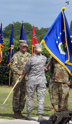 Col. Samuel E. Fiol (left) receives the 502nd Force Support Group colors from Brig. Gen. Laura L. Lenderman, 502nd Air Base Wing and Joint Base San Antonio commander, during a change of command ceremony held at the JBSA-Fort Sam Houston base flagpole July 11, where he took over for outgoing commander Col. David L. Raugh.