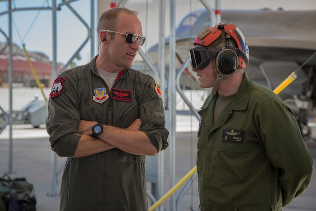 "U.S. Airman Maj. Caleb ""Skeet"" Guthman, a pilot, attached to Hill Air Force Base, Utah, discusses upcoming exercises with U.S. Marine Corps Cpl. Samuel Beddoes, an aviation ordnance technician with Marine Fighter Attack Squadron (VMFA) 122, Marine Corps Air Station (MCAS) Yuma, on MCAS Yuma, Ariz., June 26, 2018. The exercise tested, for the first time, the interoperability of loading weapon systems between the services F-35's. The U.S. Air Force operates with the F-35A Lightning II, while the U.S. Marine Corps operates with the F-35B Lightning II. (U.S. Marine Corps photo by Sgt. Allison Lotz)"