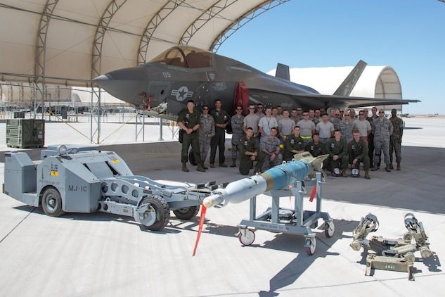 U.S. Marines with Marine Fighter Attack Squadron (VMFA) 122, Marine Corps Air Station (MCAS) Yuma, pose for a group photo with U.S. Airmen attached to the 4th Aircraft Maintenance Unit, Hill Air Force Base, Utah, during an exercise on MCAS Yuma, Ariz., June 26, 2018. The exercise tested, for the first time, the interoperability of loading weapon systems between the services F-35's. The U.S. Air Force operates with the F-35A Lightning II, while the U.S. Marine Corps operates with the F-35B Lightning II. (U.S. Marine Corps photo by Sgt. Allison Lotz)