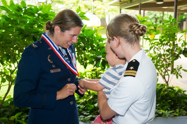 Makai Agha, of Kailua, Hawaii, and his mother, U.S. Navy Lt. Kelly Agha, right, congratulate U.S. Air Force Col. Athanasia Shinas following the 624th Regional Support Group assumption of command ceremony at Joint Base Pearl Harbor-Hickam, Hawaii, July 7, 2018.