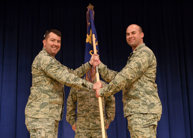 Col. William Betts, 51st Fighter Wing commander, gives the 51st Comptroller squadron guidon to Maj. Gregory White during a change of command ceremony at the Officers Club, July 2, 2018. During the ceremony, White took command of the 51st CPTS from Lt. Col. Christopher Jeffreys, 51st CPTS outgoing commander. (U.S. Air Force photo by Airman 1st Class Ilyana A. Escalona)