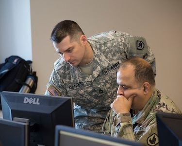 Sgt. 1st Class Samuel Anderson, Joint Force Headquarters, Washington National Guard, advises Cpt. Sameer Puri, 56th Theater Information Operations Group, during the International Collegiate Cyber Defense Invitational, July 6, 2018, at Highline Community College in Des Moines, Washington. Washington National Guard Soldiers attended the International Collegiate Cyber Defense Invitational to help educate information technology students on their responses to cyber-attacks.