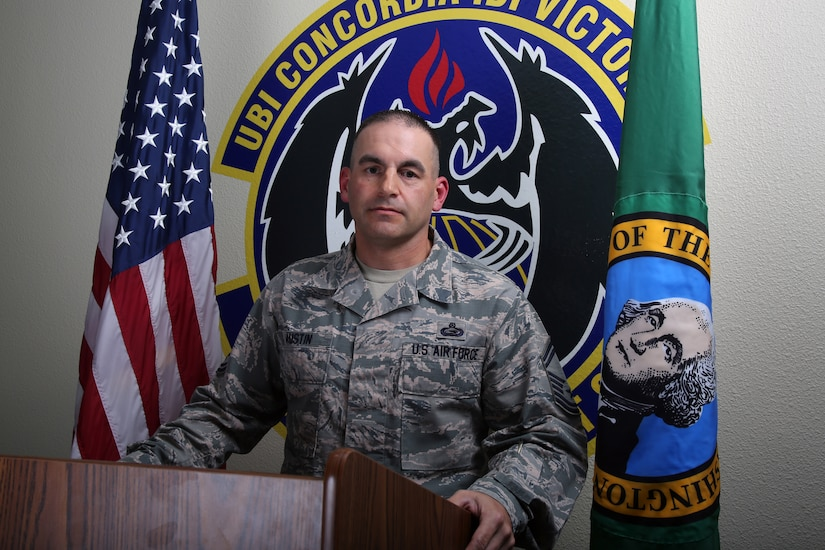 A senior enlisted airman stands behind a podium in front of flags and a unit logo.