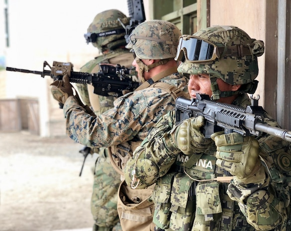 """U.S. Marines with 2nd Battalion, 1st Marine Regiment, and Mexican marines assigned to the Amphibious Marine Infantry Brigade stand security during an integrated squad exercise with as they navigate the infantry immersion trainer during Rim of the Pacific exercise at Marine Corps Base Camp Pendleton, California, July 9, 2018. The IIT provided the Marines with """"hands on"""" practical application of tactical skills and decision making in an immersive, scenario-based training environment. RIMPAC demonstrates the value of amphibious forces and provides high-value training for task-organized, highly-capable Marine Air-Ground Task Forces enhancing the critical crisis response capability of U.S. forces and partners globally. Twenty-five nations, 46 ships, five submarines, about 200 aircraft and 25,000 personnel are participating in RIMPAC from June 27 to Aug. 2 in and around the Hawaiian Islands and Southern California."""