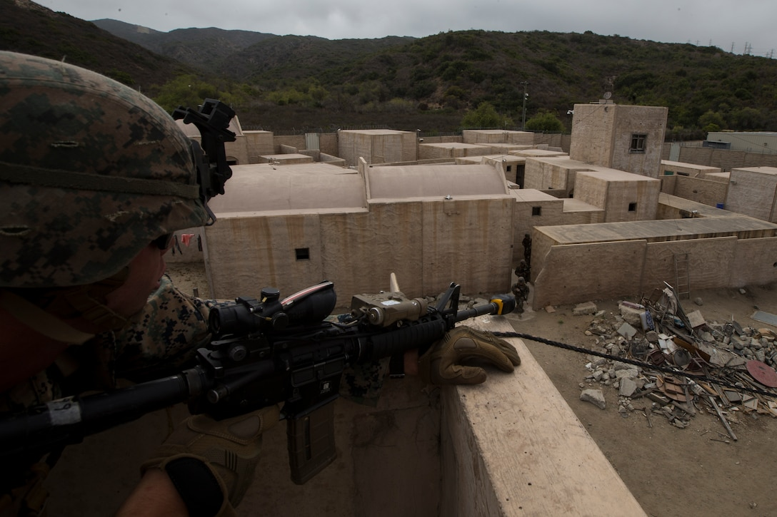 """U.S. Marine Corps Lance Cpl. Riley McQuaid, an infantry Marine with 2nd Battalion, 1st Marine Regiment, provides security for another fireteam at an Infantry Immersion Trainer during Rim of the Pacific exercise on Marine Corps Base Camp Pendleton, California, July 10, 2018. The IIT provided the Marines with """"hands on"""" practical application of tactical skills and decision making in an immersive, scenario-based training environment. RIMPAC demonstrates the value of amphibious forces and provides high-value training for task-organized, highly capable Marine Air-Ground Task Forces enhancing the critical crisis response capability of U.S. forces and partners globally. Twenty-five nations, 46 ships, five submarines, about 200 aircraft and 25,000 personnel are participating in RIMPAC from June 27 to Aug. 2 in and around the Hawaiian Islands and Southern California."""
