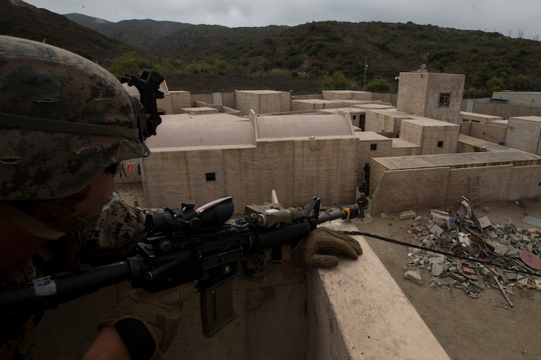 "U.S. Marine Corps Lance Cpl. Riley McQuaid, an infantry Marine with 2nd Battalion, 1st Marine Regiment, provides security for another fireteam at an Infantry Immersion Trainer during Rim of the Pacific exercise on Marine Corps Base Camp Pendleton, California, July 10, 2018. The IIT provided the Marines with ""hands on"" practical application of tactical skills and decision making in an immersive, scenario-based training environment. RIMPAC demonstrates the value of amphibious forces and provides high-value training for task-organized, highly capable Marine Air-Ground Task Forces enhancing the critical crisis response capability of U.S. forces and partners globally. Twenty-five nations, 46 ships, five submarines, about 200 aircraft and 25,000 personnel are participating in RIMPAC from June 27 to Aug. 2 in and around the Hawaiian Islands and Southern California."