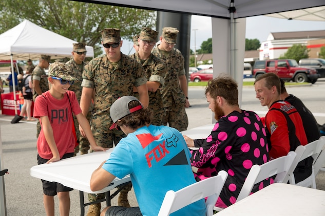 Service members and their families receive autographs from freestyle motocross performers during the exposition portion of a Semper Ride event on Marine Corps Base Camp Lejeune, June 26. Educating service members on the correct way to ride a motorcycle is the main mission of Semper Ride gatherings. (U.S. Marine Corps photo by Lance Cpl. Nathan Reyes)