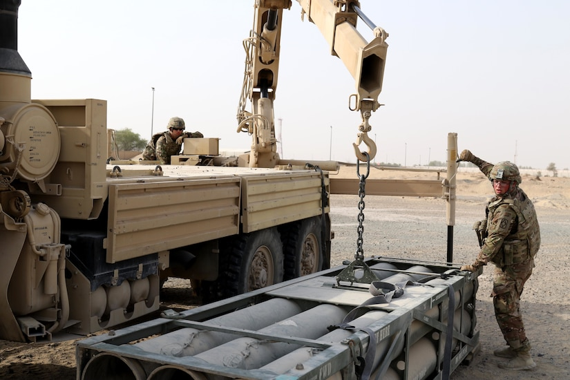 Pfc. Austin Crocker (right), High Mobility Artillery Rocket System crewmember for Bravo Battery, 1st Battalion, 14th Field Artillery Regiment, 65th Field Artillery Brigade, Task Force Spartan, signals to Pfc. Miguel Rodriguez, also a HIMARS crewmember, as they unload a pod for the Golden Sparrow exercise on June 29, 2018.