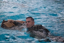 A Marine with Headquarters and Support Battalion, Marine Corps Installations East, Marine Corps Base Camp Lejeune, participate in the basic swim qualification course at the Area 5 Training Tank on MCB Camp Lejeune, N.C., July 2, 2018. The Marine Corps Water Survival Training Program employs water survival skills of increasing levels of ability designed to help Marines survive in the water. (U.S. Marine Corps photo by Lance Cpl. Ashley D. Gomez)