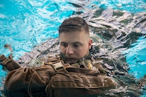 A Marine with Headquarters and Support Battalion, Marine Corps Installations East, Marine Corps Base Camp Lejeune, participates in the basic swim qualification course at the Area 5 Training Tank on MCB Camp Lejeune, N.C., July 2, 2018. The Marine Corps Water Survival Training Program employs water survival skills of increasing levels of ability designed to help Marines survive in the water. (U.S. Marine Corps photo by Lance Cpl. Ashley D. Gomez)