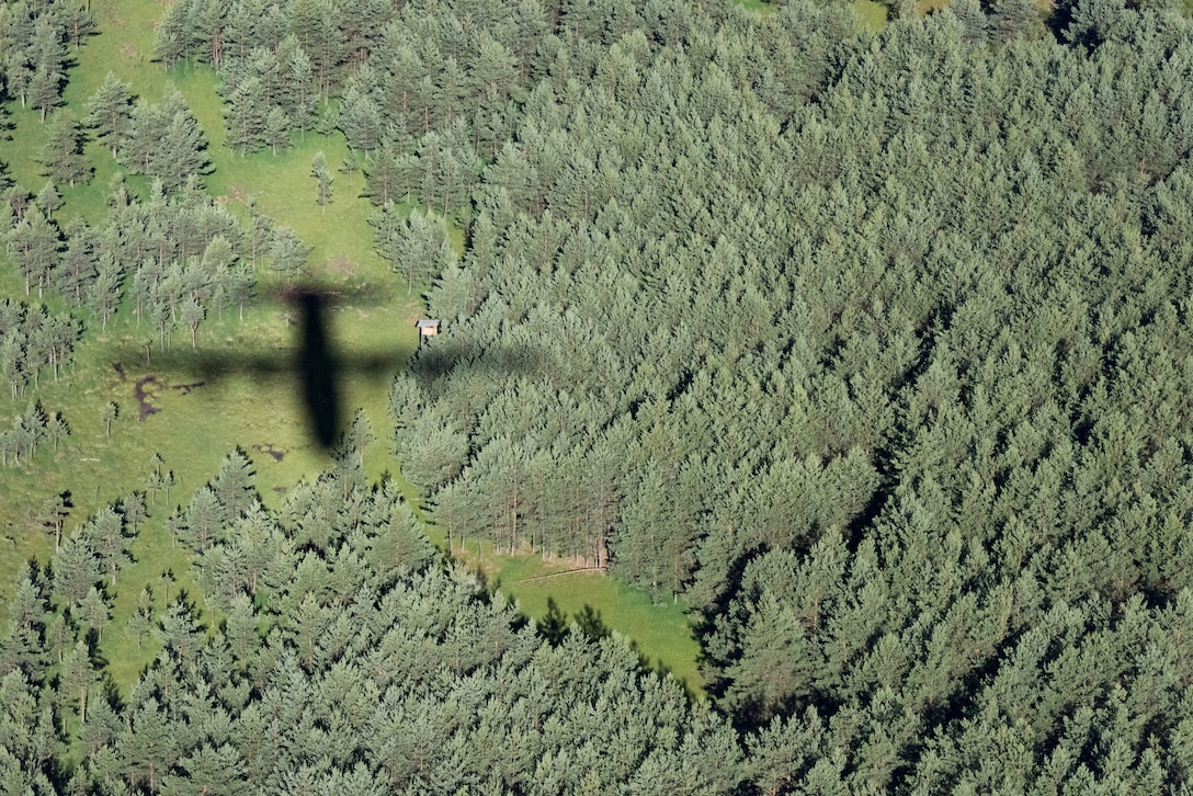 The shadow of a C-130J Super Hercules flies over the dense woods of Germany, July 2, 2018. This particular C-130J led the formation during an exercise that involved four other C-130Js. Once the pilots have led a formation long enough, they are recognized as multi-element flight lead qualified pilots. Multi-element flight lead qualified pilots help ensure the 37th Airlift Squadron is prepared to accomplish one of its primary missions: aerial delivery and mass on the drop-zone.