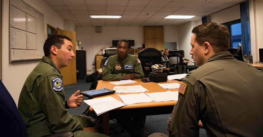U.S. Air Force Capt. Joshua Rodriguez, 86th Operational Support Squadron Current Operations officer, discusses with Maj. Willie Lloyd, 37th Airlift Squadron director of staff, and Capt. James Denoyer, 37th Airlift Squadron resource advisor, about the logistics of carrying out an exercise where five C-130J Super Hercules aircraft flew together in formation over Germany, on July 2, 2018. In total, 21,800 pounds of training cargo were airdropped on Bunker DZ in eastern Germany near United States Army Garrison Grafenwoehr.