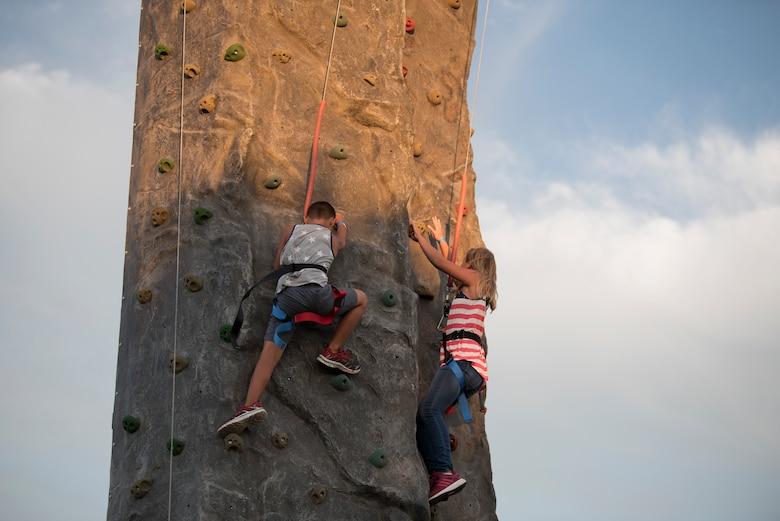 Two children climb up a rock wall prior to an Intel drone light show at Travis Air Force Base, Calif., July 5, 2018. The event featured numerous activities including music, bounce houses and an eight minute light show with 500 drones. (U.S. Air Force photo by Tech. Sgt. James Hodgman)