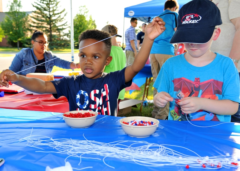 Ezekiel GIllard, age 4, and Porter Schuschke, age 6, create bracelets at the children's arts and crafts table during Freedom Fest, July 3, 2018, at Grand Forks Air Force Base, North Dakota. Several activities were available for children during the event to include bounce houses, crafts and games. (U.S. Air Force photo by Staff Sgt. Marcy Copeland