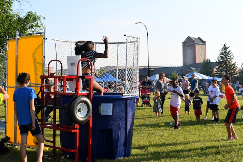Children take turns getting dropped into a dunk tank by friends at the Freedom Fest hosted on July 3, 2018, on Grand Forks AFB, North Dakota. More than 300 Airmen, friends and families attended the event to celebrate Independence Day. (U.S. Air Force photo by Airman 1st Class Elora J. Martinez)