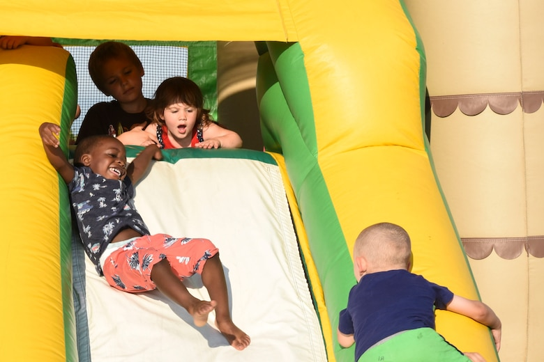 Children enjoy the inflatable slide at Freedom Fest July 3, 2018, on Grand Forks Air Force Base, North Dakota. The slide, along with the rest of the inflatable playground, was open to children of all ages, and gave parents a chance to enjoy the event with while occupying their little ones. (U.S. Air Force photo by Airman 1st Class Melody Wolff)