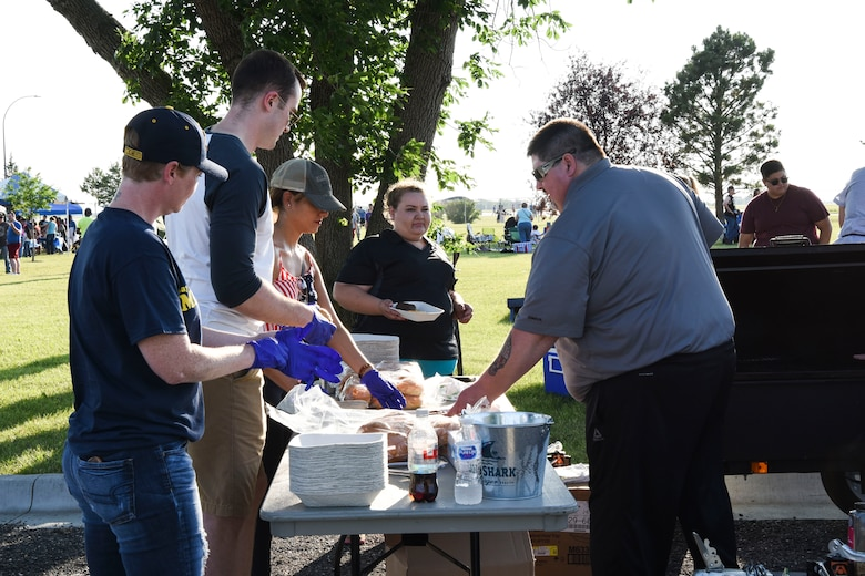 Volunteers, along with employees from J.R. Rockers, assist with cooking hamburgers and providing beverages for guests at Freedom Fest July 3, 2018, on Grand Forks Air Force Base, North Dakota. Because the initial food truck was unable to attend, these volunteers came to the rescue, and there were over 300 hamburgers sold at this event. (U.S. Air Force photo by Airman 1st Class Melody Wolff)