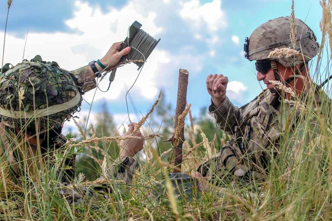 An American and U.K. soldier place a claymore.