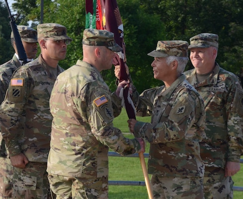 Lt. Col. Paul D. Lang (left) accepts the unit colors from Col. Shauna L. Snyder, commander, Medical Professional Training Brigade while the outgoing commander Lt. Col. John F. Detro looks on.