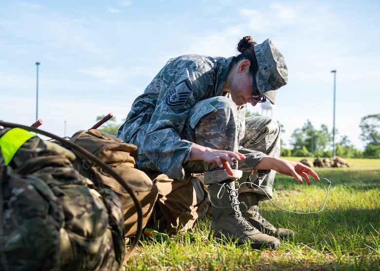 Master Sgt. Kay Williams, 919th Special Operations Security Forces Squadron, laces her boots after she and her team paused to care for their feet following a seven-mile ruck march May 5, 2018 near Duke Field, Fla.