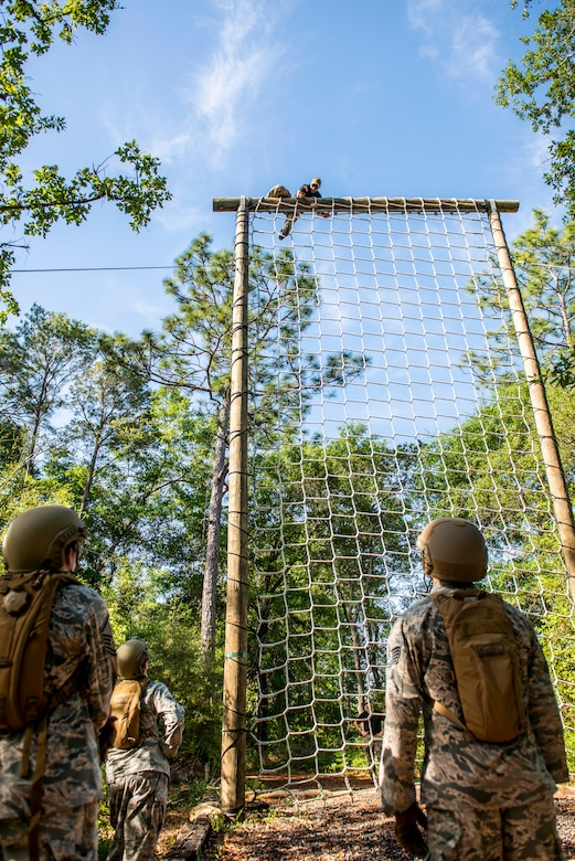 Airmen from the 919th Special Operations Security Forces Squadron watch as a training cadre member demonstrates proper techniques for the cargo net obstacle May 5, 2018 on Eglin Air Force Base, Fla.