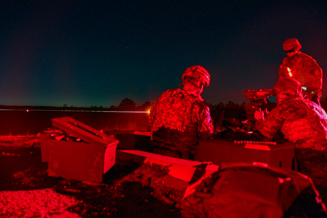 Soldiers fire weapons at night.