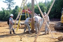 Staff Sgt. Brian Wood, 445th Civil Engineer Squadron structural journeyman (far left) and members of the Air National Guard's 189th CES from Little Rock Air Force Base, Arkansas, place a beam for a pole barn at Camp Kamasa, Crystal Springs, Mississippi, June 6, 2018.