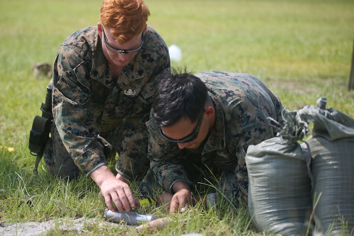 Sgt. Josh Alexander, left, and Staff Sgt. Steve Gomez measure a piece of ordnance during a tool familiarization range aboard MCAS Beaufort July 11. The Marines conducted the range to maintain proficiency on the tools and equipment they use. Alexander and Gomez are with MCAS Beaufort explosive ordnance disposal.