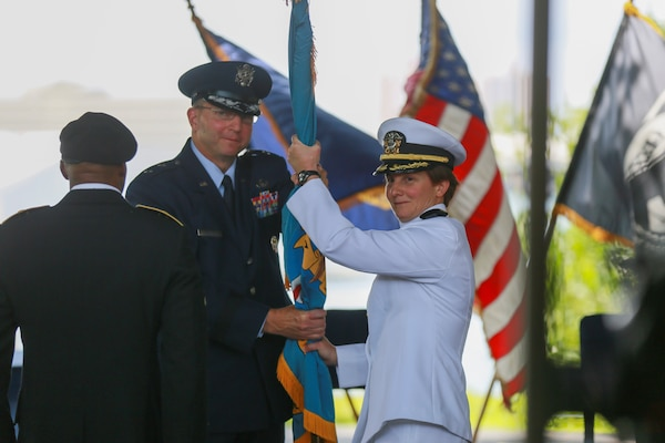 DLA Logistics Operations Director Air Force Maj. Gen. Mark Johnson passes the DLA flag to incoming DLA Pacific Commander Navy Capt. Kristin Acquavella, during a change of command at Nob Hill on historic Ford Island, Pearl Harbor, Hawaii July 10.(Photo by Marine Cpl. Patrick Mahoney)