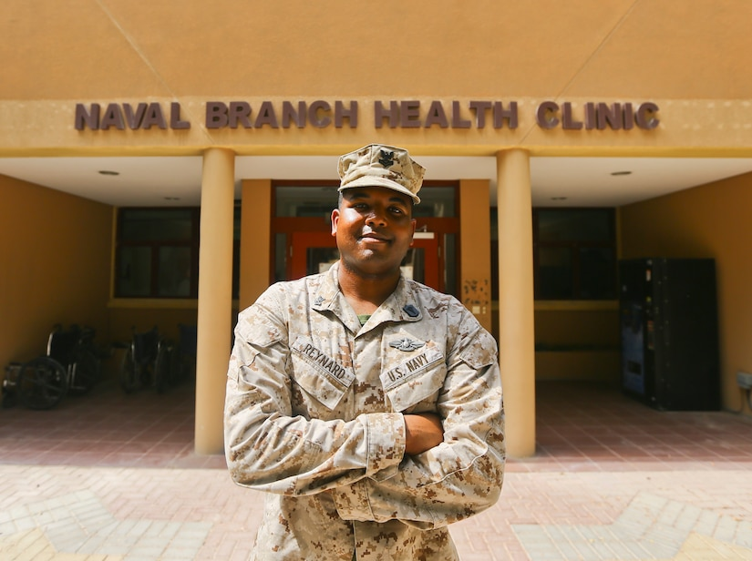 A sailor poses for a photo in front of a medical clinic.