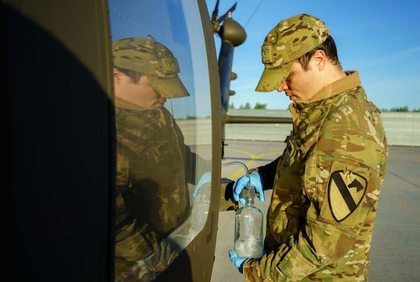 An Army soldier removes fuel from an aircraft for testing .