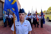 Airman Mackenzie Lakatos, a munitions apprentice student at the 363rd Training Squadron, stands at attention as a flight of Airmen carrying state flags perfects their spacing before the 34th Annual Kell House Museum Fourth of July and Most Patriotic Parade in downtown Wichita Falls, Texas, July 4, 2018. (U.S. Air Force photo by John Ingle)
