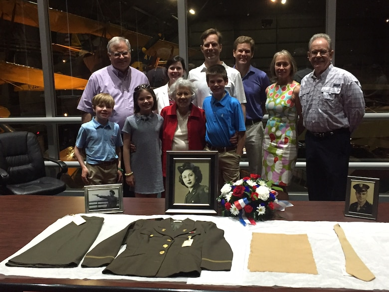 Yolanda 'Tipi' Minnehan stands with two of her three children, some of their children and some of her great-grandchildren July 6 at the National Museum of the U.S. Air Force as they admire her uniform artifacts from the Women's Army Auxiliary Corps, later the Women's Army Corps. U.S. Air Force Col. Barney Minnehan, whose final active-duty assignment was at Wright-Patterson AFB, is pictured far right. (Skywrighter photo/Amy Rollins)