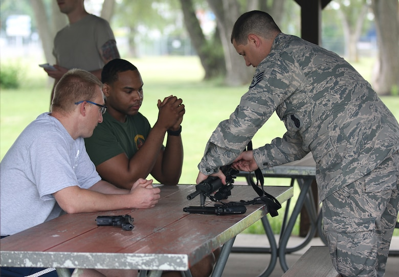 Senior Airman Markell Lawson and Staff Sgt. Steven Branham, 445th Aerospace Medicine Squadron, receive weapons handling training from Staff Sgt. Jordan Helphrey, 445th Security Forces Squadron, as a part of a team building exercise here June 6, 2018.