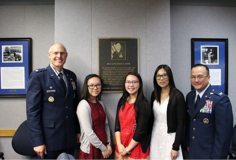 (Left to right) Lt. Col. William Kostan, Kaci Moy, Jodi Moy, Akina Moy and Col. Andrew Torelli gather in front of a plaque honoring Col. James J. Moy. Members of Air Mobility Command's intelligence community recently dedicated a conference room in Moy's honor. Moy, an Illinois native and member of the Illinois Air National Guard, died in 2013 after a battle with cancer. (U.S. Air Force photo)