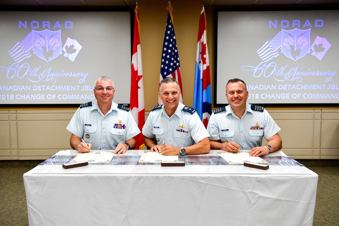 Canadian Brig. Gen. Sylvain Menard (center), Continental U.S. North American Aerospace Defense Region (CONR) deputy commander, presides over the Western Air Defense Sector Canadian Detachment change of command. Lt. Col. Michael Fawcett (left) assumes command from the outgoing commander, Lt. Col. Matthew Wappler (right), during the ceremonial signing of the change of command scrolls July 10, 2018. (U.S. Air National Guard photo by Kimberly D. Burke)