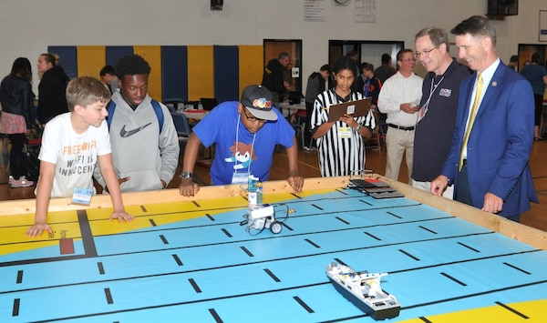 IMAGE: KING GEORGE. Va. (June 25, 2018) - Rep. Rob Wittman (R-Va.) observes middle school students deploy a robot they designed, built, and programmed to deliver humanitarian aid, rotate troops and transport an electromagnetic railgun to the deck of a Navy ship at the 2018 STEM Summer Academy. Students briefed their mentors, teachers, and visitors, including Wittman, on how they overcame a variety of Navy focused problems by designing, building, and programming LEGO Mindstorm robots to solve a variety of Navy focused problems.