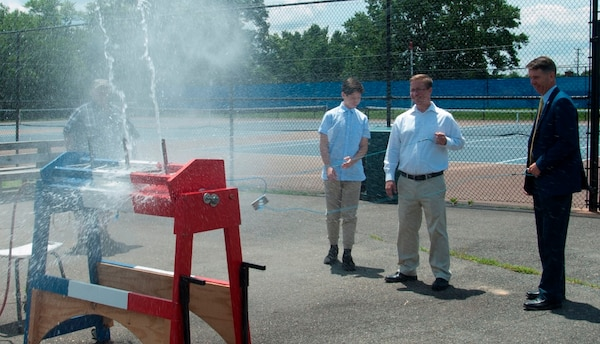 IMAGE: KING GEORGE. Va. (June 25, 2018) - Rep. Rob Wittman (R-Va.) fires a water rocket with a middle school student and a Navy scientist-mentor at the 2018 STEM Summer Academy sponsored by Naval Surface Warfare Center Dahlgren Division. The water rockets were constructed and calibrated by students in conjunction with an aerospace engineering activity. The teachers and mentors inspired students to develop their teamwork and problem-solving skills in math and science throughout the camp.