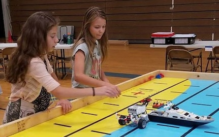 IMAGE: KING GEORGE. Va. (June 28, 2018) - Middle school students prepare to deploy robots they designed, built, and programmed to respond to 10 missions - including the delivery of humanitarian aid, rotating troops and transporting an electromagnetic railgun to the deck of a Navy ship - at the 2018 STEM Summer Academy. The students briefed their mentors, teachers, and visitors on how they overcame a variety of Navy focused problems with STEM, creativity, communication, and teamwork throughout the week-long academy.