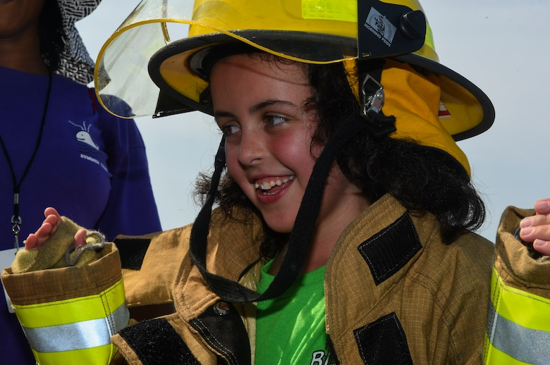 Elizabeth Wyatt, age 8, attempts to put on a firefighter uniform as quickly as possible during a Science, Technology, Engineering, Art and Mathematics (STEAM) event July 12, 2018, at the emergency management building on Joint Base Charleston, S.C.