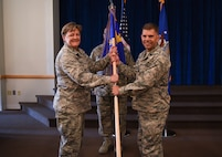 Colonel Tricia Van Den Top, 90th Mission Support Group commander, passes the guidon to Lt. Col. Raymond Spohr, 90th Communications Squadron commander, during the 90th CS change of command ceremony July 13, 2018 at Trails End on F.E. Warren Air Force Base, Wyo. The ceremony signified the transition of command from Lt. Col. Josef Chesney. (U.S. Air Force photo by Airman 1st Class Abbigayle Wagner)