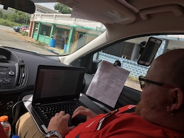 A member of the Pittsburgh Temporary Power Mission in Puerto Rico inputs data in the Englink system while in the field.