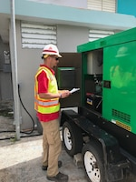 A member of the Pittsburgh District temp. power team inspects a generator at a facility.
