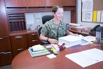 "Lieutenant Commander Jamie Rivas studies one of the many ""turnover"" binders to get up to speed in her new role as Public Works Officer, aboard Marine Corps Logistics Base Barstow, Calif.,  July 2. The native of Bryan, Ohio, is taking over for outgoing LCDR Jeffrey Patton."
