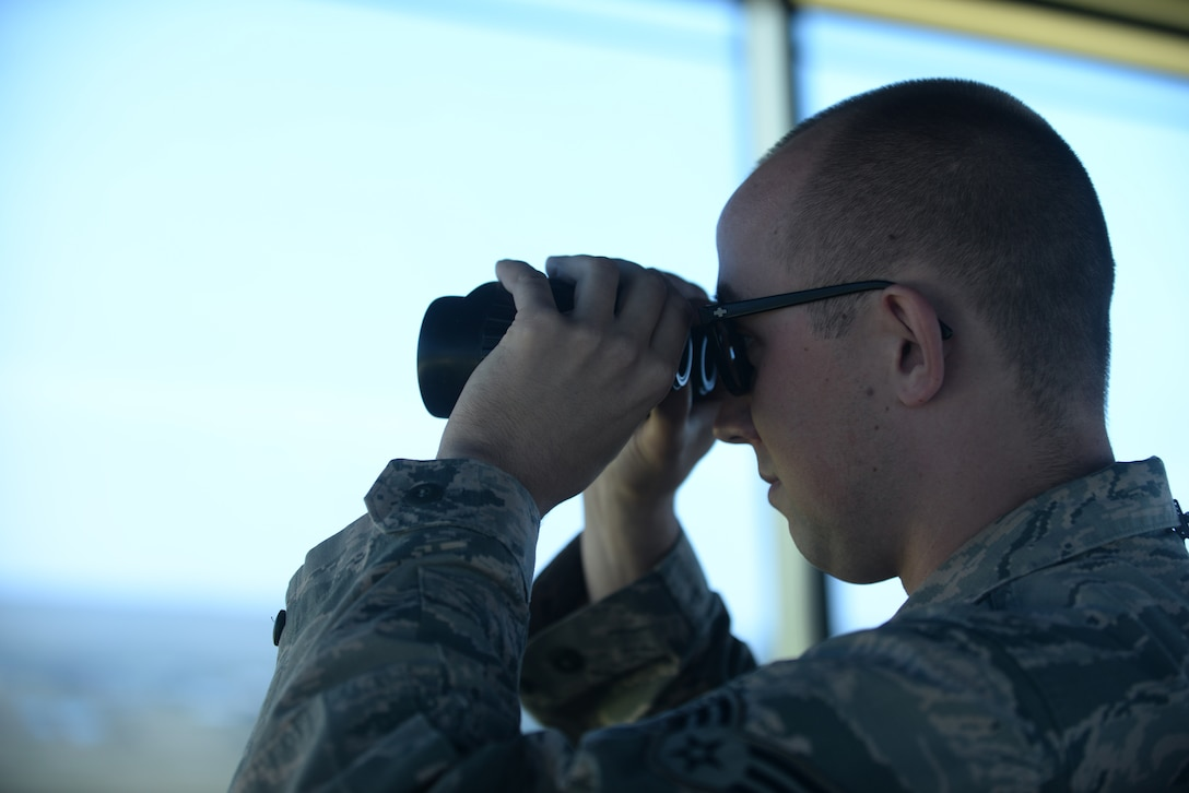 Senior Airman Grant Krause, a 28th Operations Support Squadron air traffic control journeyman, monitors at the flight line through binoculars inside the air traffic control tower at Ellsworth Air Force Base, S.D., July 10, 2018. Air traffic controllers are qualified to work on both the tower, which coordinates movement on the flight line, and the radar approach control team, which coordinates aircraft movement in the sky. (U.S. Air Force photo by Airman 1st Class Nicolas Z. Erwin)